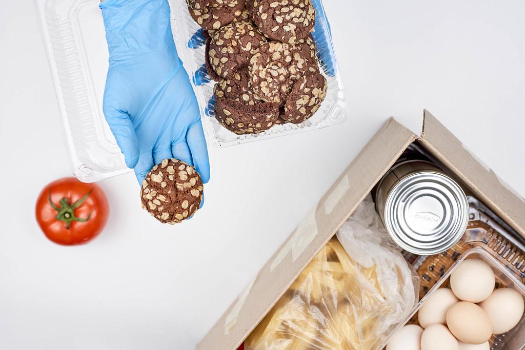 Hand mit Einmalhandschuh serviert Keks aus einem Karton mit Lebensmittelspende wie bei der Tafel