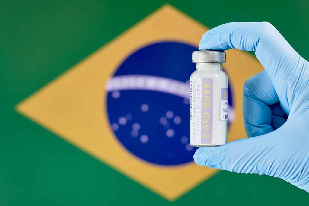 Hand mit Einmalhandschuhen hält Corona Impfstoff-Fläschchen vor der Flagge Brasiliens