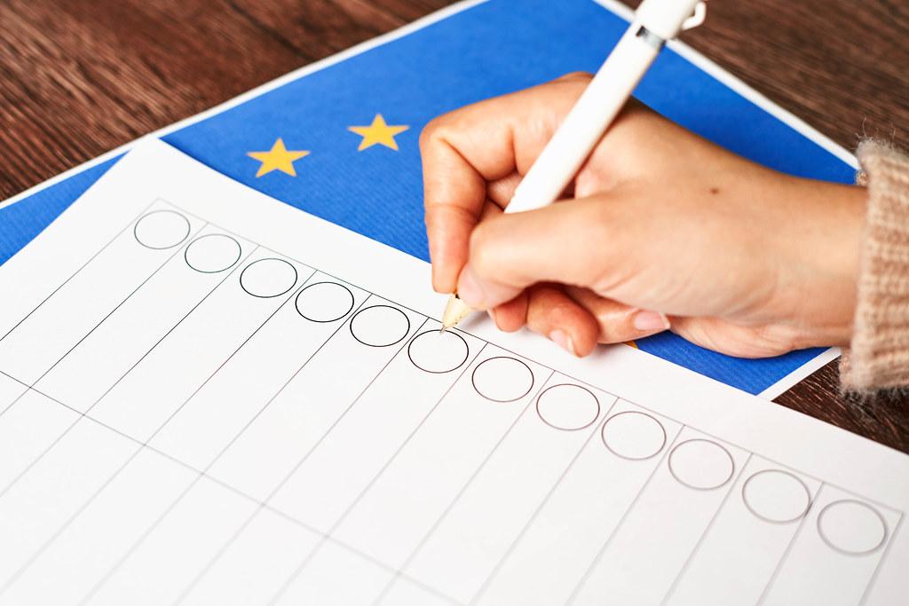 Hand mit Kugelschreiber vor einem leeren Stimmzettel mit der europäischen Flagge auf dem Tisch