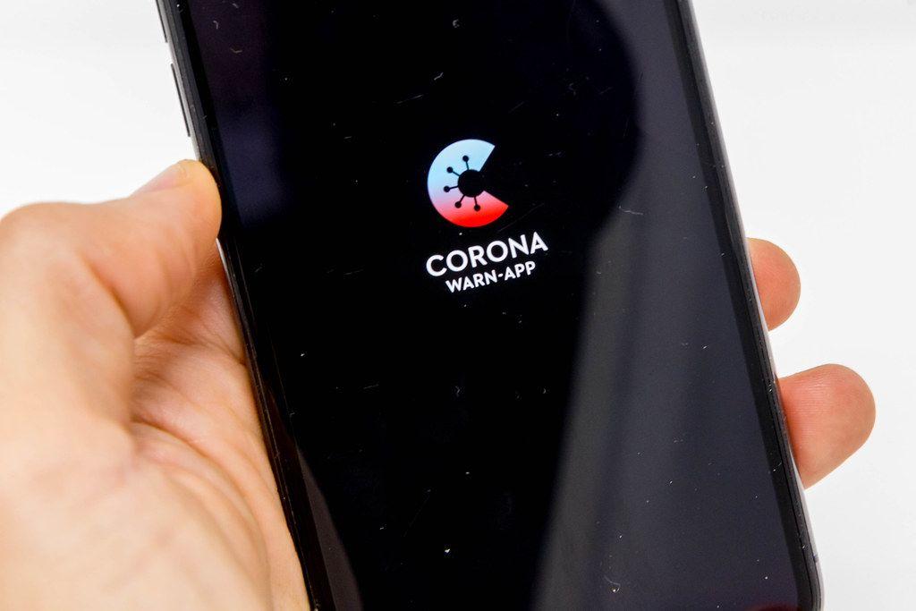 Hand mit Smartphone Bildschirm, der den Logo der deutschen Corona Warn-App zeigt
