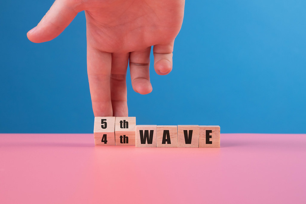 Hand of a man who turning a wooden blocks with text 4th Wave to 5th Wave