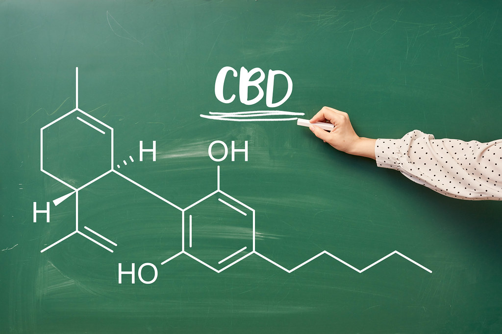 Hand of laboratory worker writing chemical formula of CBD on the chalkboard