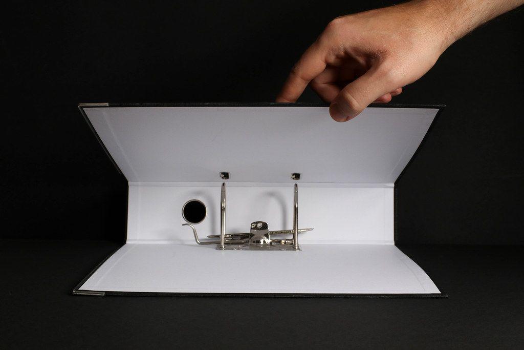 Hand opening empty folder on black background