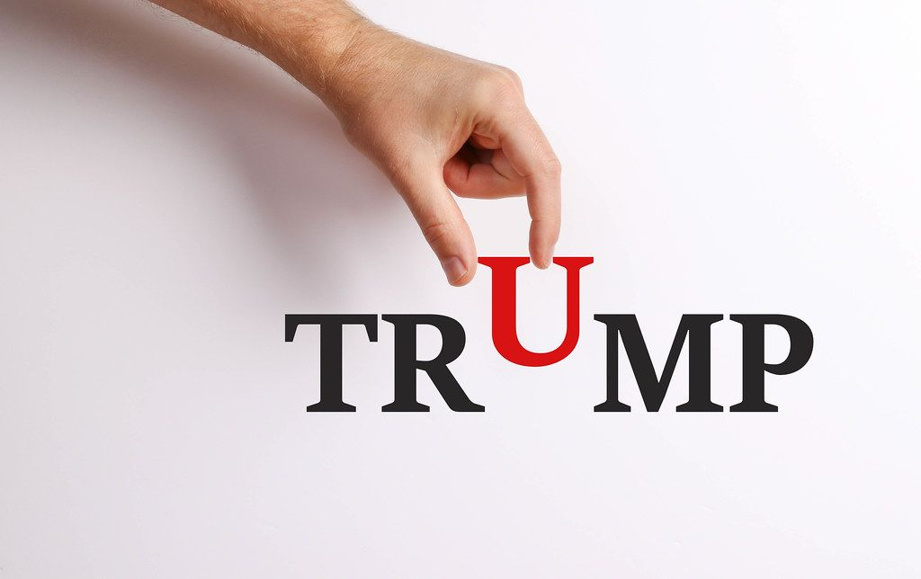 Hand pick up 'U' from Trump text