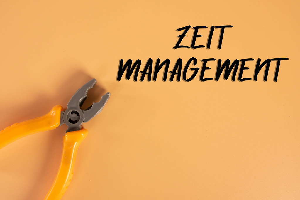 Hand pliers with Zeit Management text on orange background