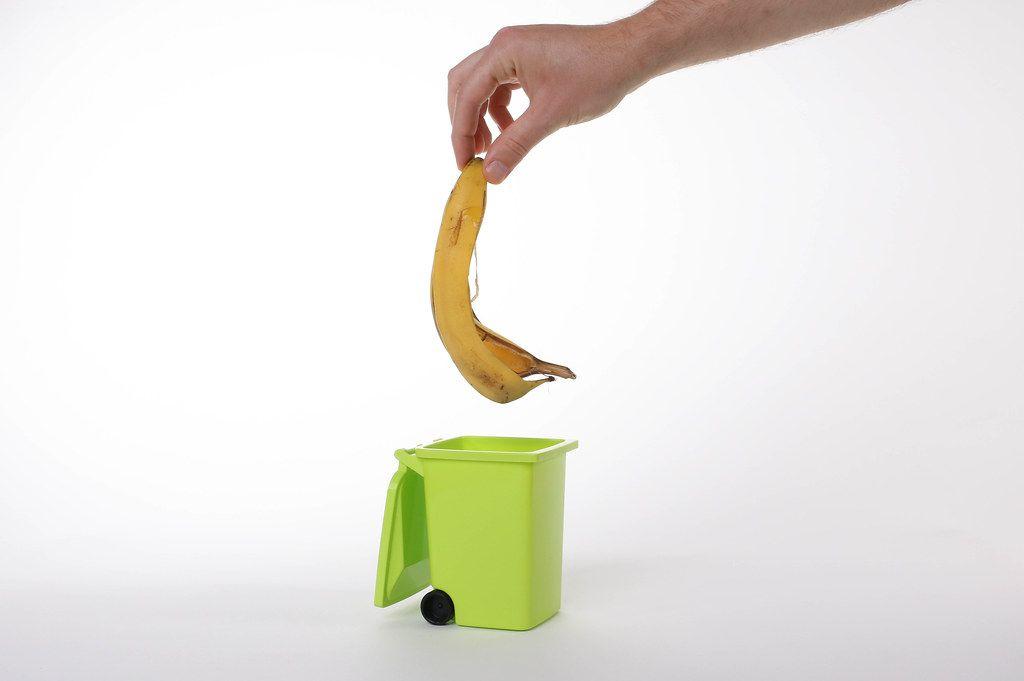Hand putting banana peel in recycling bio bin