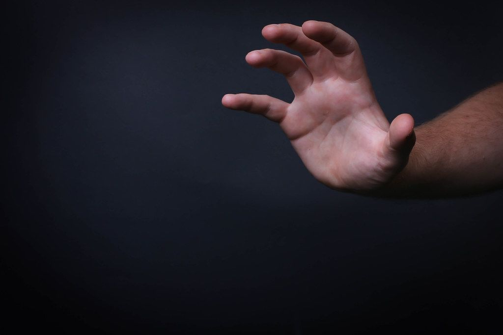 Hand reaching out on black background