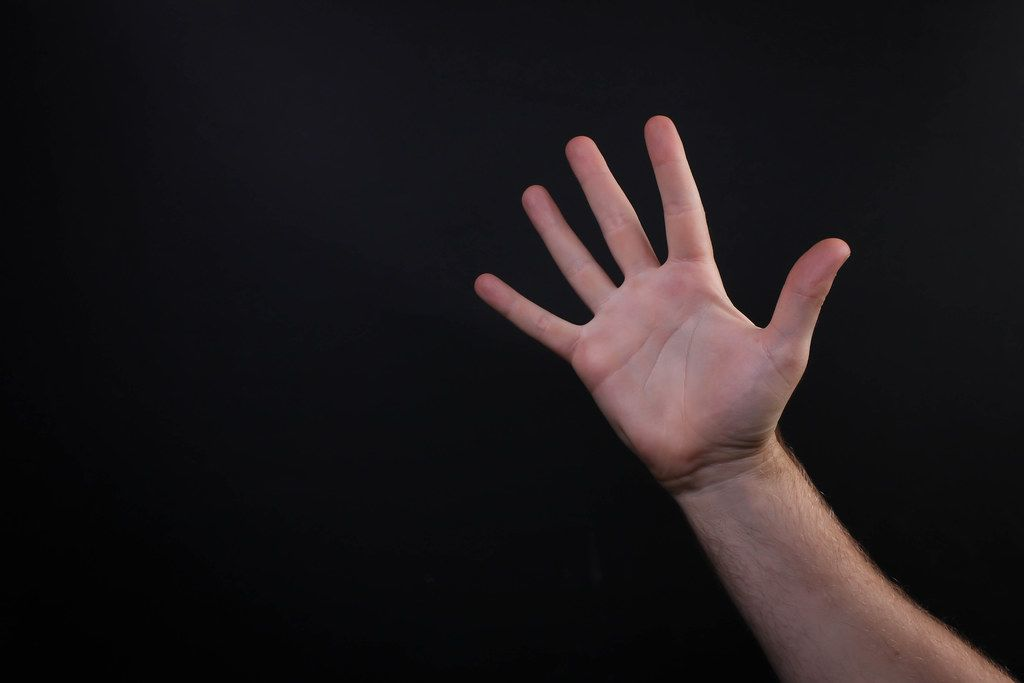 Hand showing number five on black background