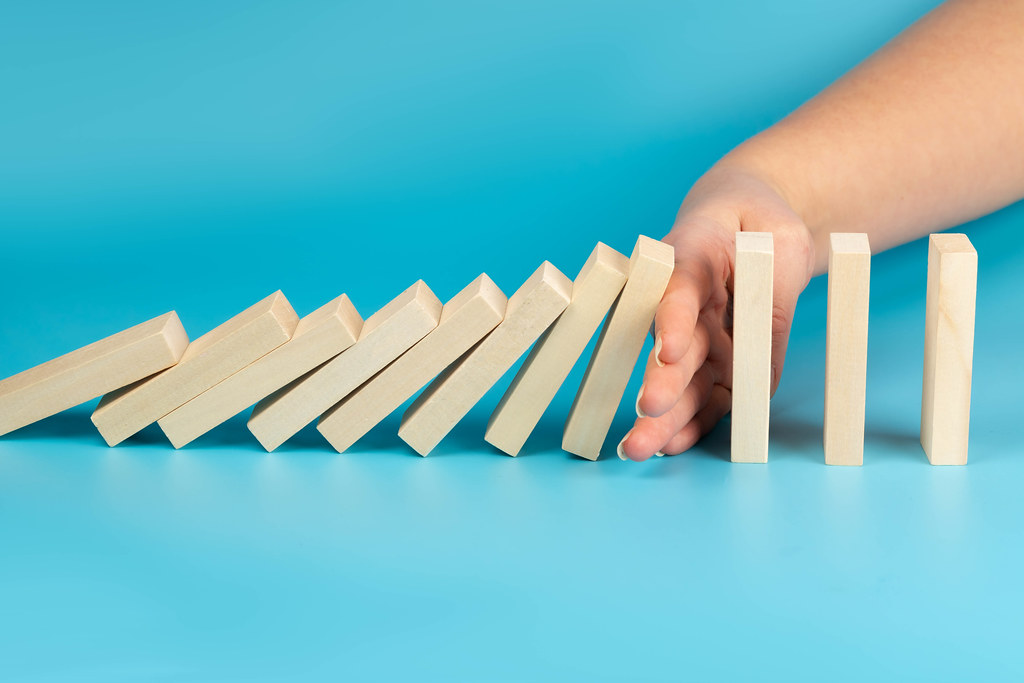 Hand stopping wooden blocks from falling in the line of domino, blue background