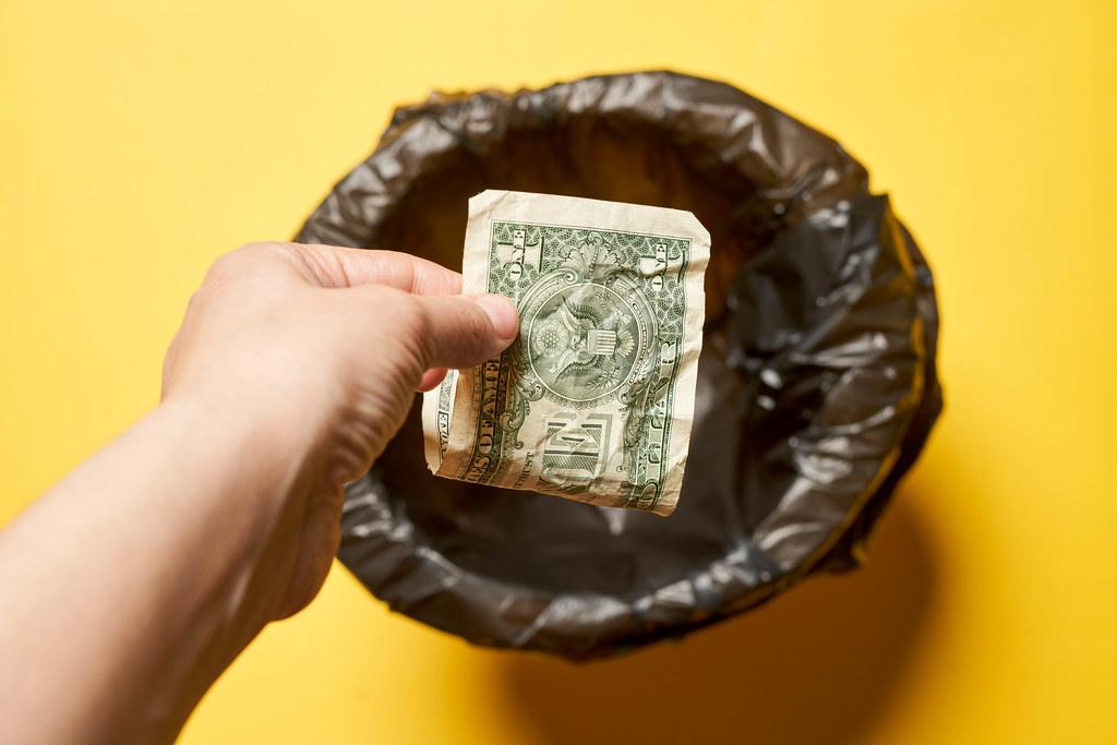 Hand throwing money into trash bin