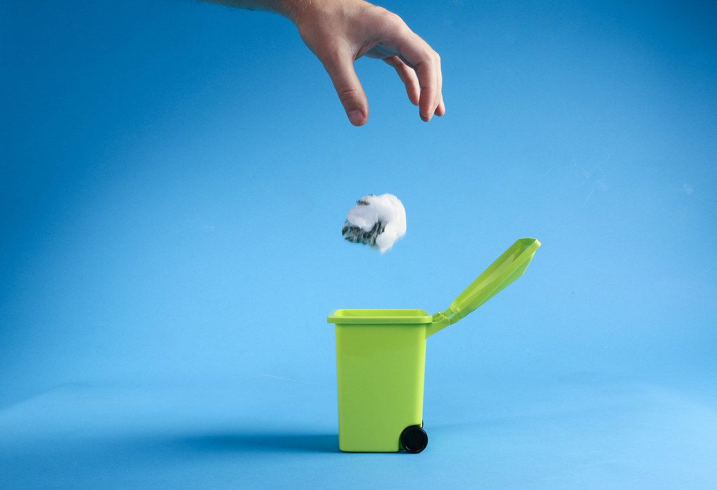 Hand throwing plastic bag into trash can on blue background