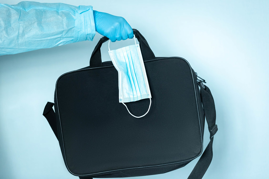 Hand with gloves holding face mask and bag, medical and healthcare concept