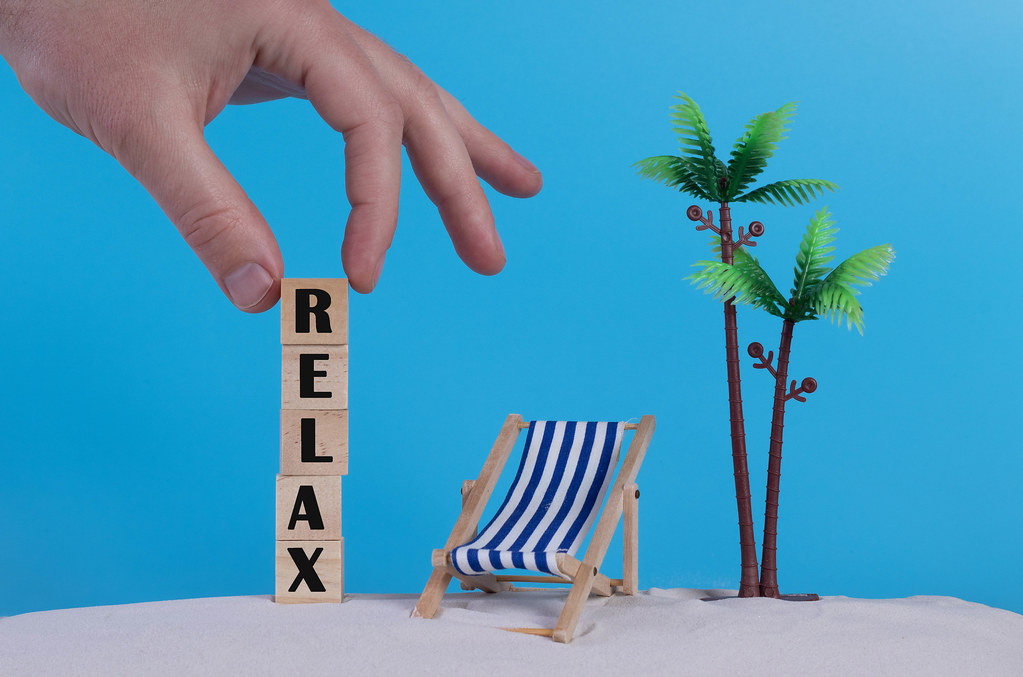 Hand with wooden blocks wiht Relax text and beach chair on blue background