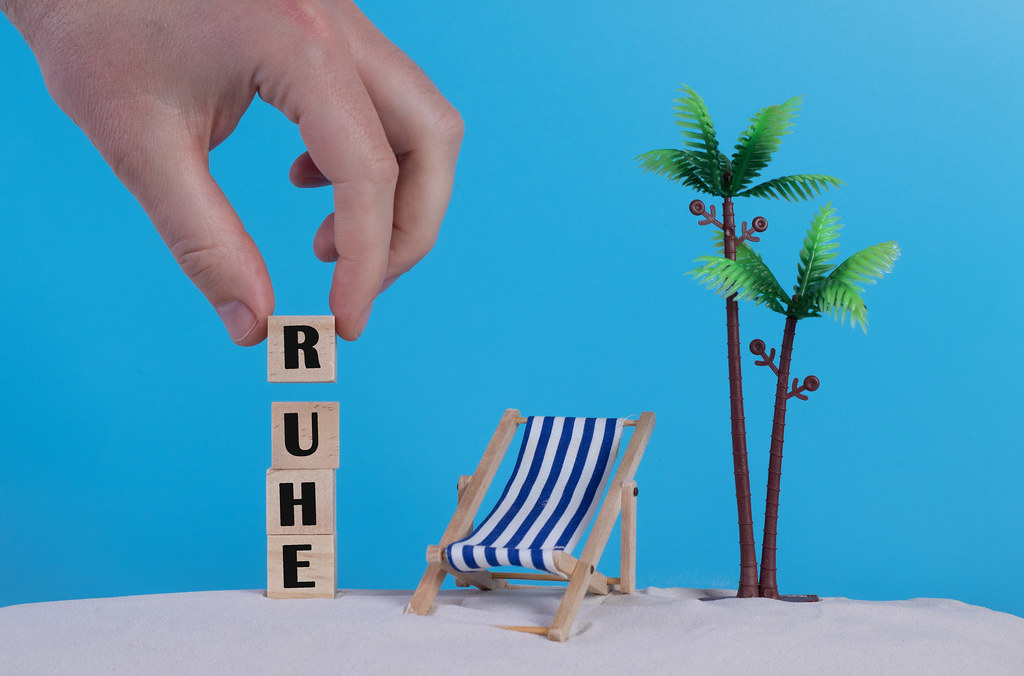 Hand with wooden blocks wiht Ruhe text and beach chair on blue background