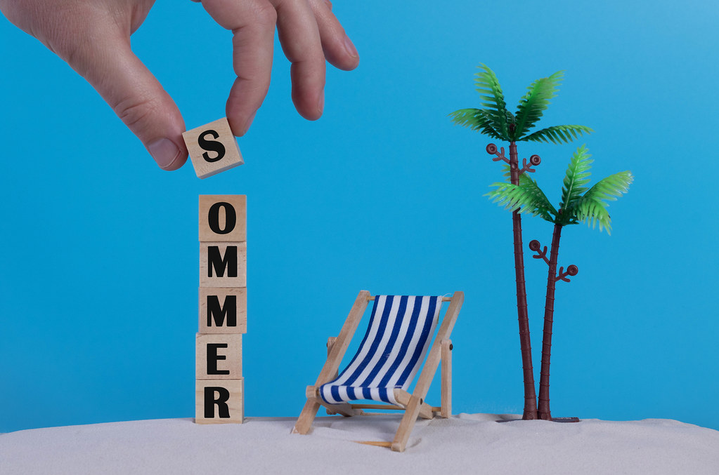 Hand with wooden blocks wiht Sommer text and beach chair on blue background