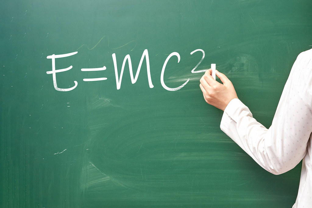 Hand writing well-known E=mc2 physical formula on chalkboard