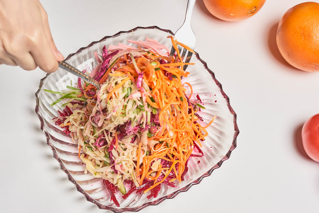 Hände mit Besteck mischen einen bunten Salat in einer quadratischen Glasschüssel