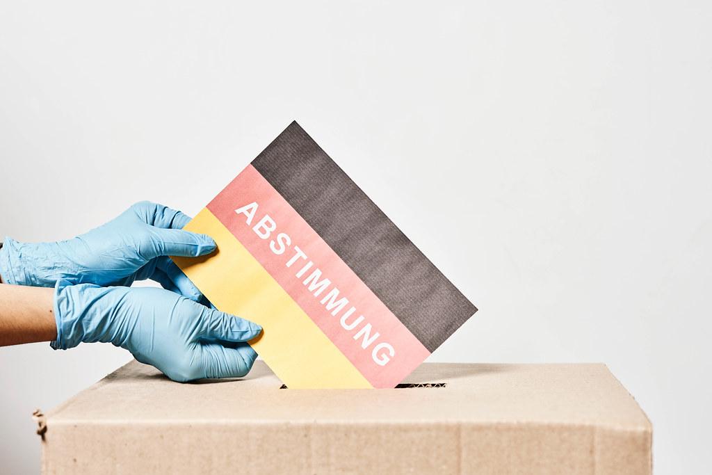 """Hände mit Einweghandschuhen werfen deutsche Flagge und Schrift """"Abstimmung"""" in die Wahlurne ein"""