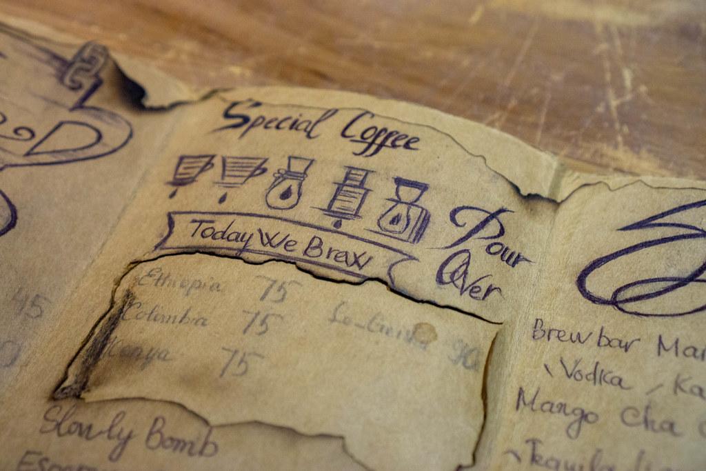 Handgeschriebene Getränkekarte mit Zeichnungen und Preisen im Vintage-Style auf einem Holztisch in einem Cafe Nahaufnahme