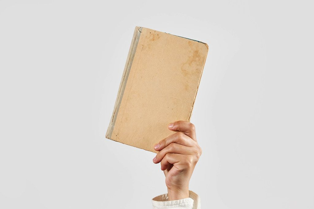 Hands hold a book. Distance education, or self-education during COVID-19 quarantine