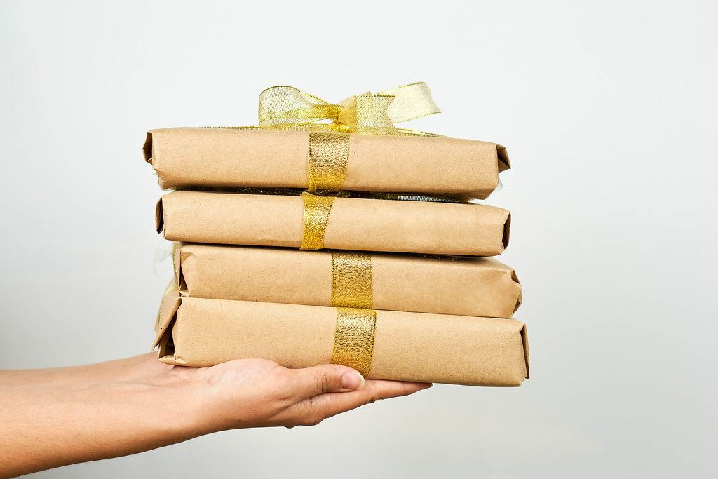 Hands holding a stack of brown paper packages tied with ribbon