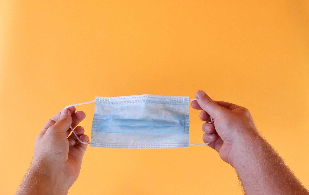 Hands holding medical face mask on orange background
