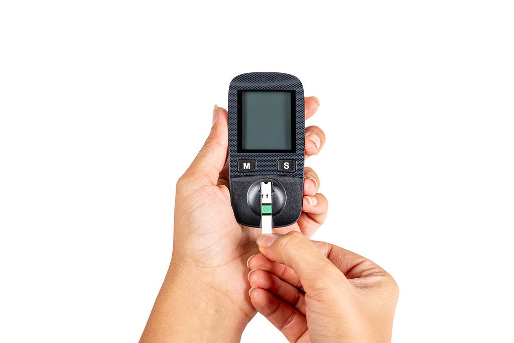 Hands holds blood glucose meter with test strip on white background
