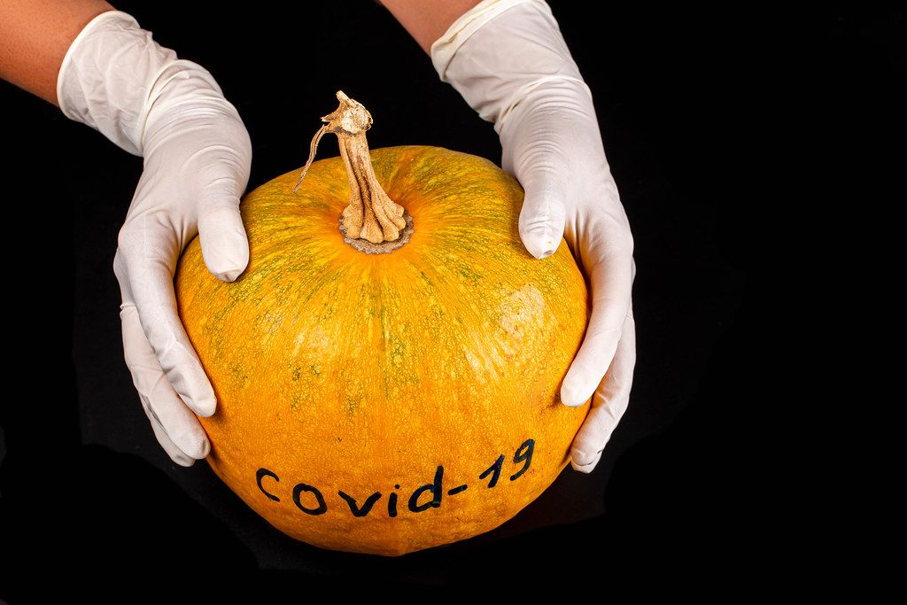 Hands in gloves hold an orange pumpkin with the inscription Covid-19 on a black background