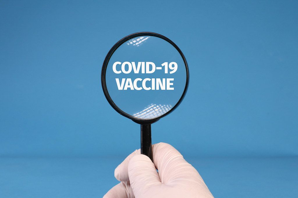 Hands in medical gloves holding magnifying glass over Covid-19 Vaccine text