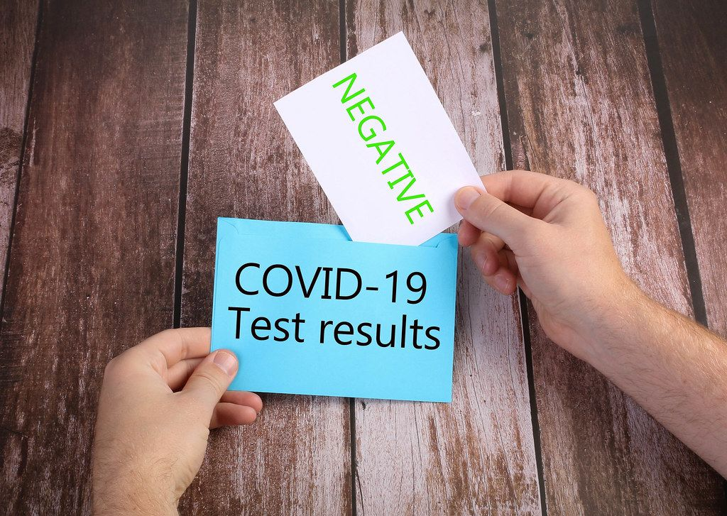 Hands opening blue envelope with Negative Covid-19 results