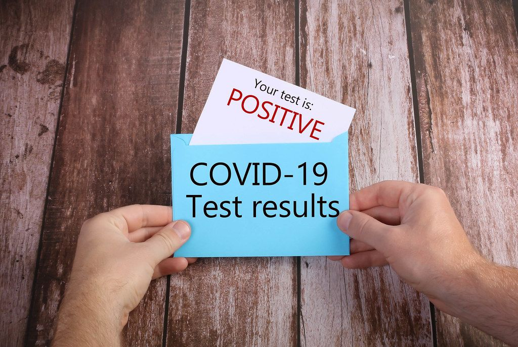 Hands opening blue envelope with Positive Covid-19 results