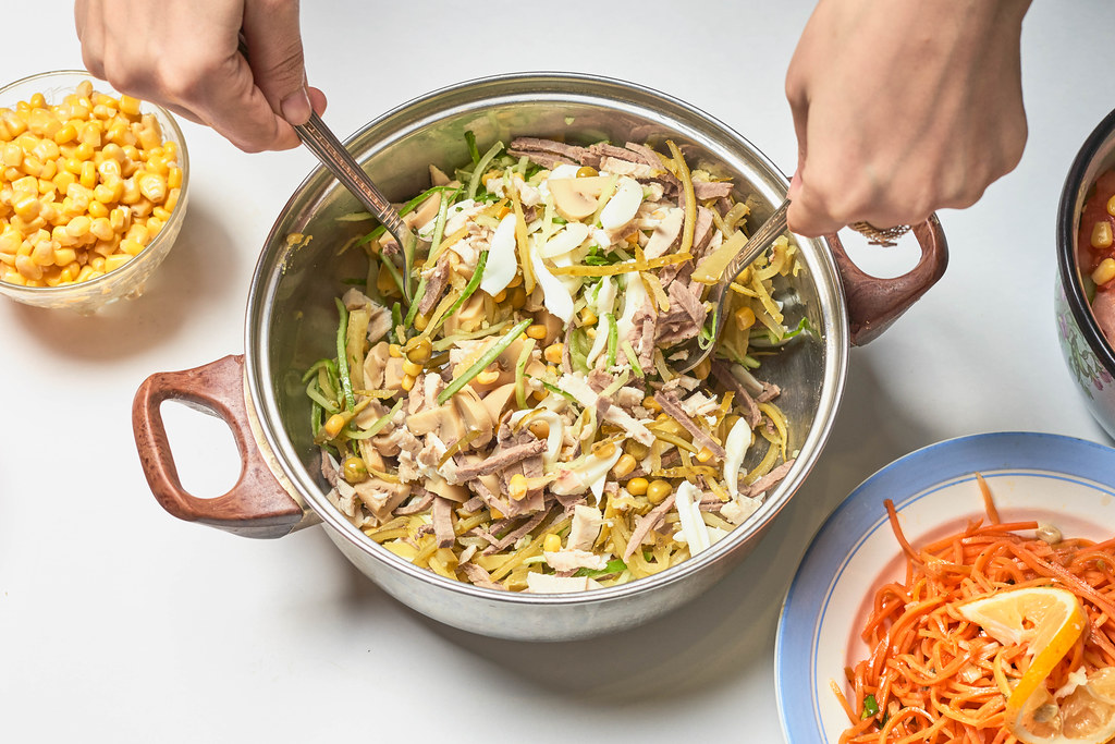 Hands using cutlery to mix the ingredients in a pot: mais, cucumber and meat cut in strips