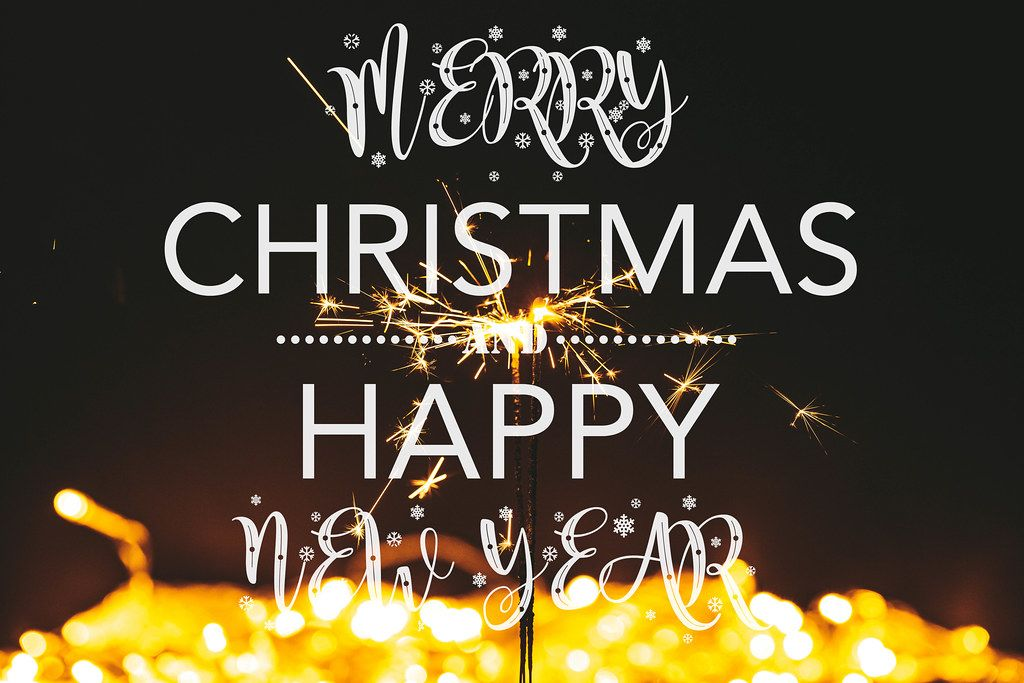 Happy Christmas and New Year on golden bokeh background with sparklers