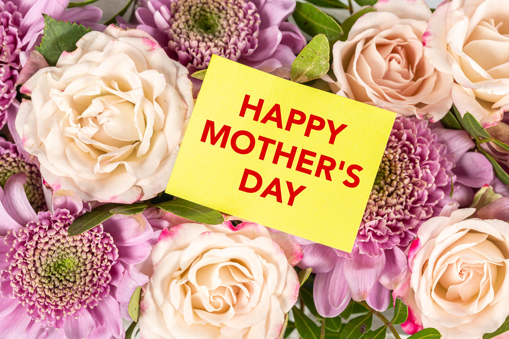 Happy mothers day greeting card on flowers background, top view