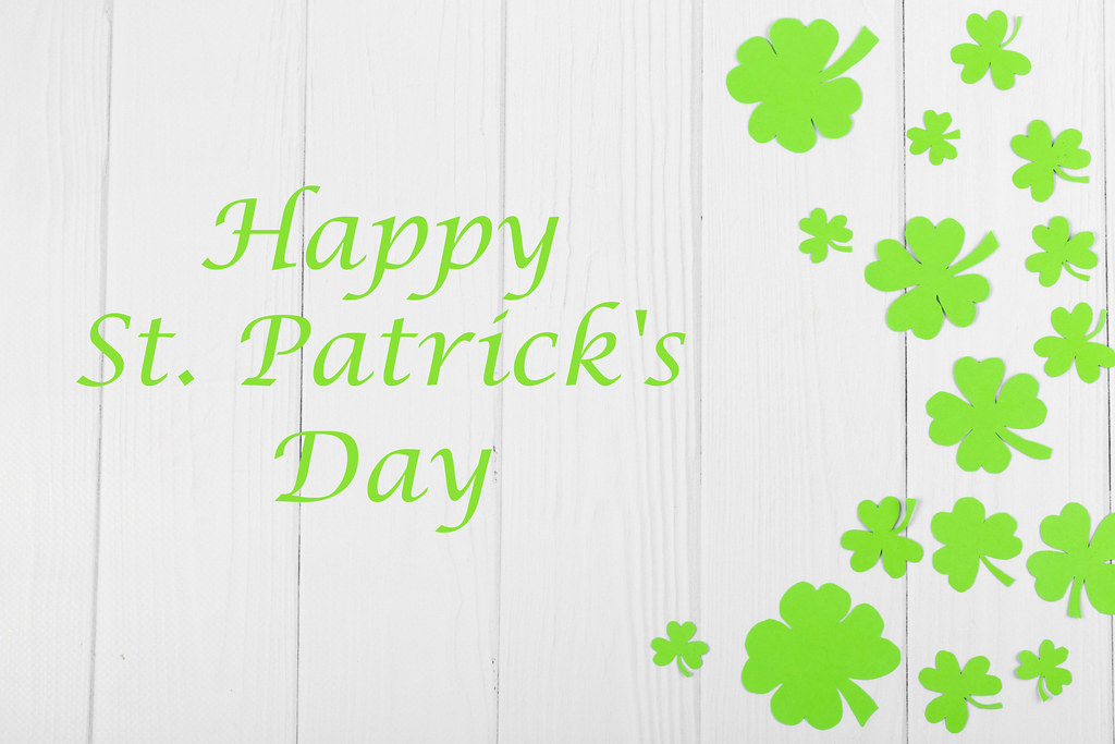 Happy saint patrick's day greeting card with traditional symbol-shamrock and four-leafed clover on wooden background