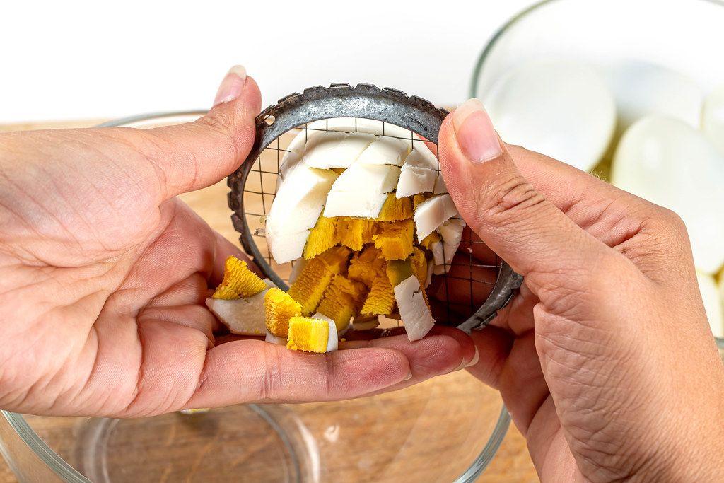 Hard-boiled egg cut on egg slicer in female hands