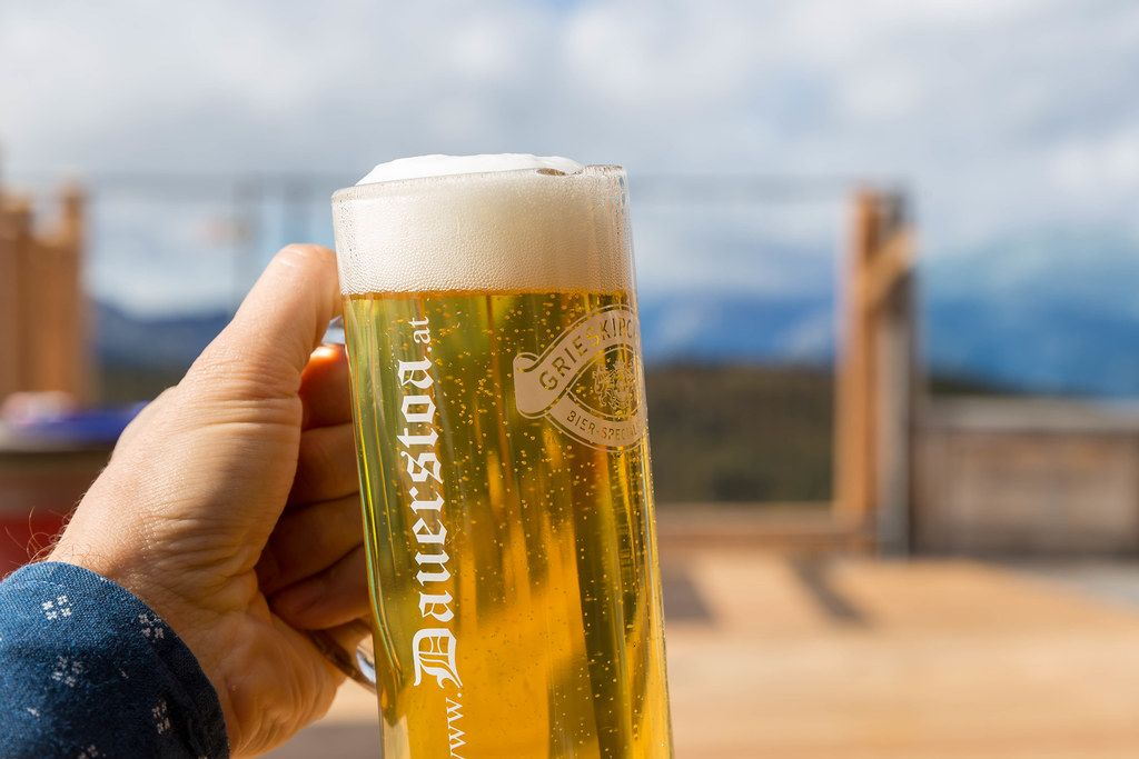 Having a beer in the mountains: hand holding glass of beer with foam on the terrace of Dauerstoa hut