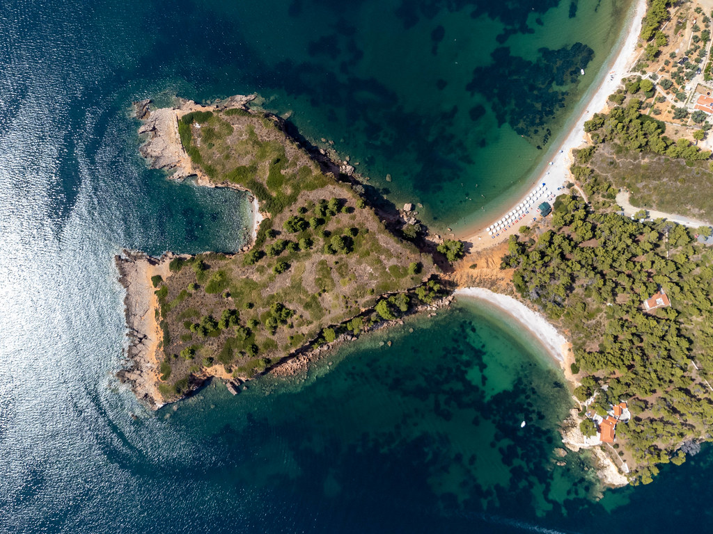 Headland forming a bay and separating two beaches: drone photo of the cliff at Kokkinokastro, Alonnisos