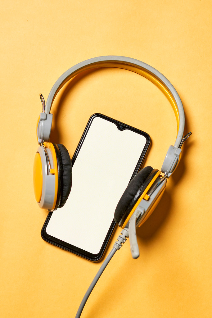 Headphones and smartphone with blank screen on yellow background