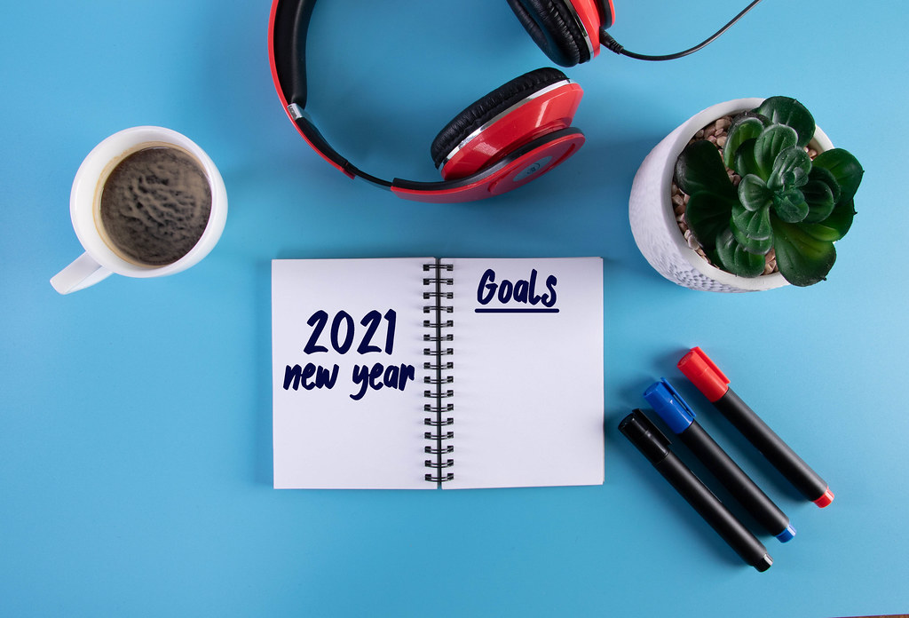 Headphones, flower and notebook with 2021 New Year Goals text