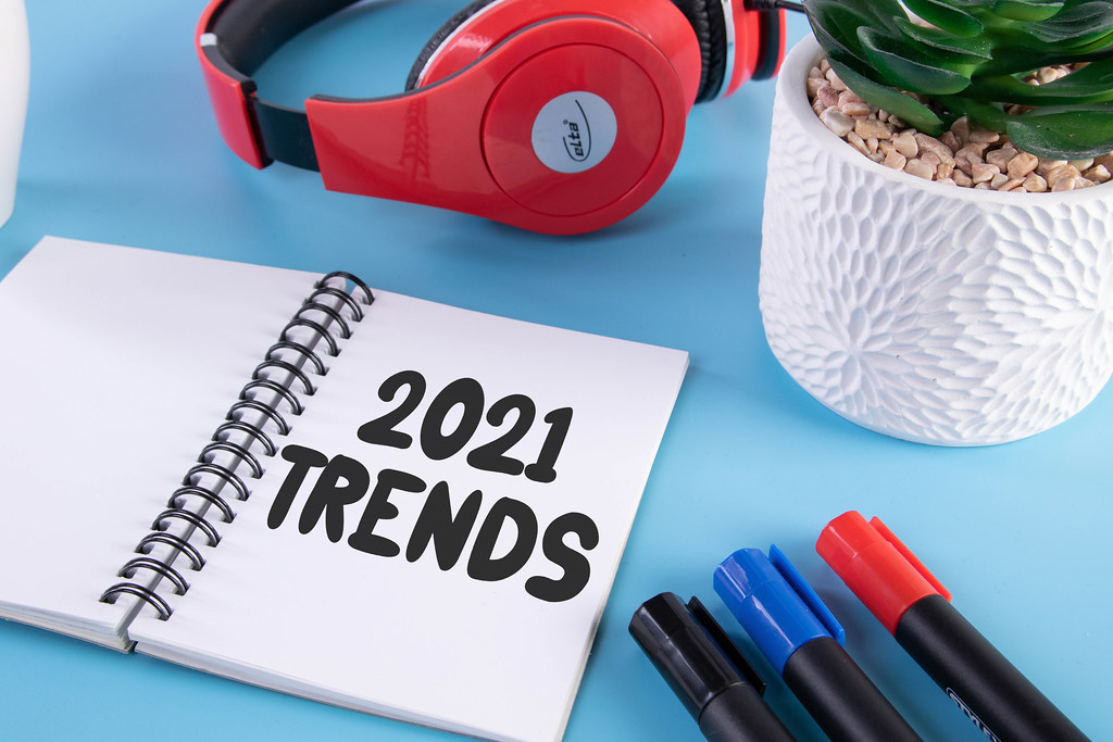 Headphones, flower and notebook with 2021 Trends text