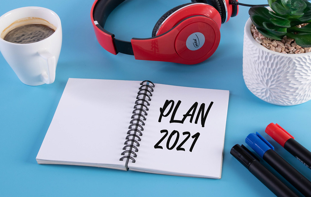 Headphones, flower and notebook with Plan 2021 text