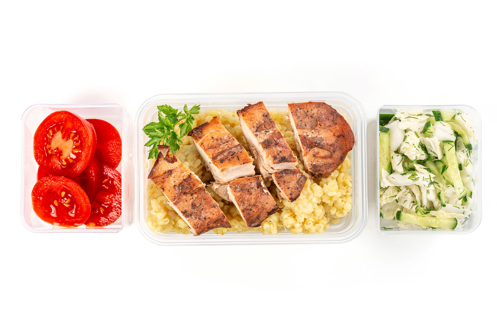 Healthy balanced lunch box on white background, top view, home food for office concept