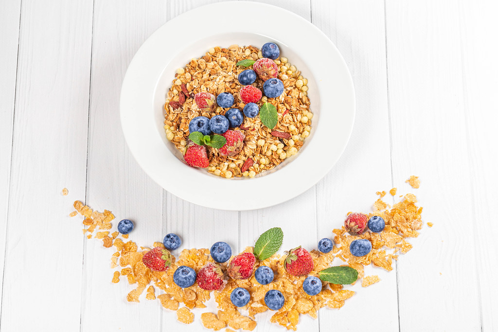 Healthy breakfast background with cereal flakes, strawberries, blueberries and mint on a white wooden table