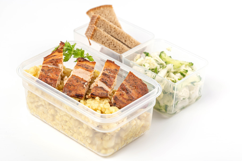 Healthy diet lunch boxes with vegetables salad, chicken fillet and bulgur porridge