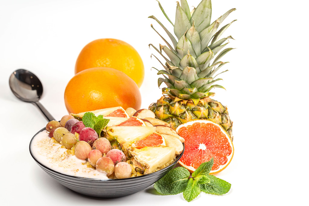 Healthy food concept - porridge with fresh fruits, berries and nuts on white background with pineapple, grapefruit and mint