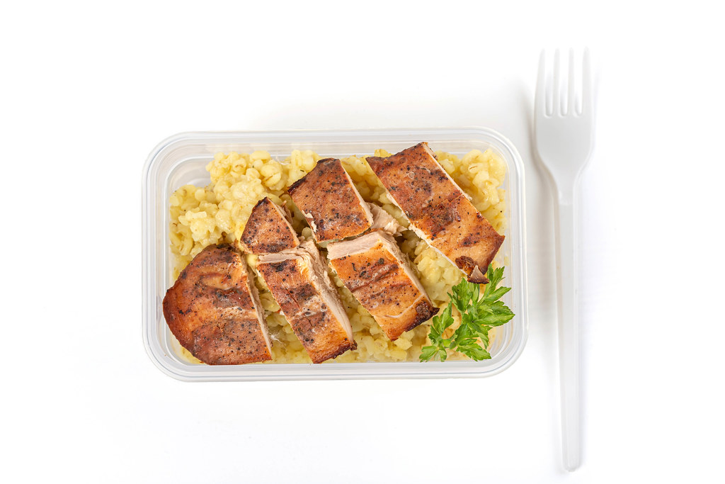 Healthy food container - boiled bulgur with baked chicken fillet, top view