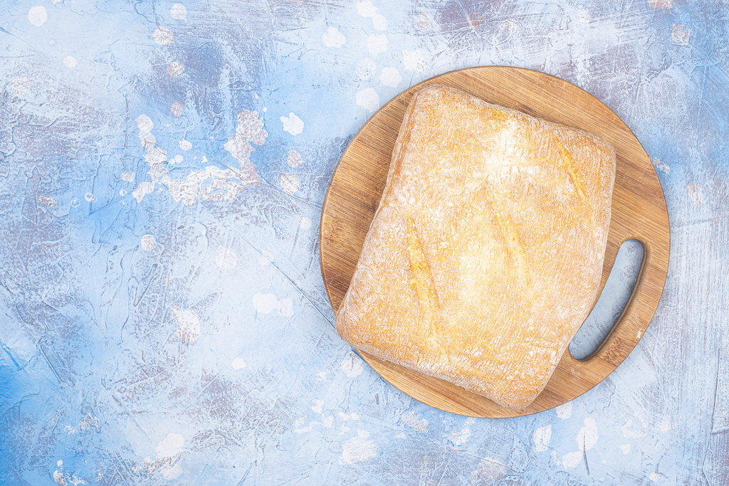 Healthy Homemade Bread on the wooden board with blue background