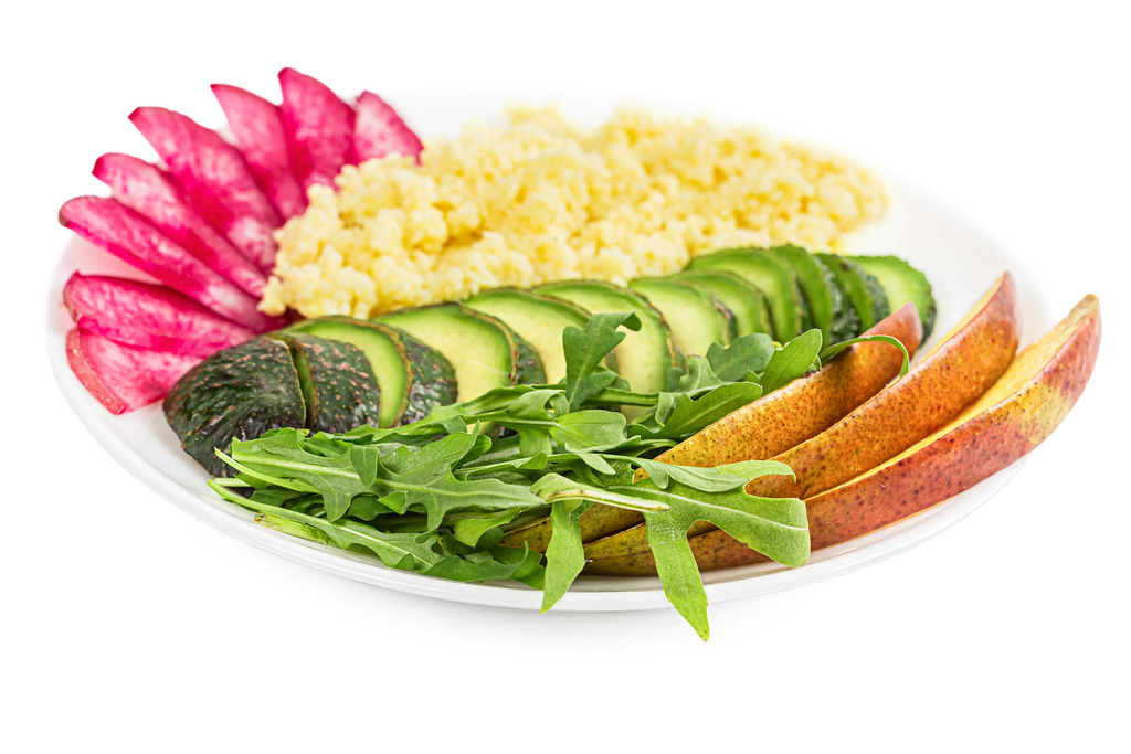 Healthy lunch with couscous porridge, vegetables, arugula and mango pieces