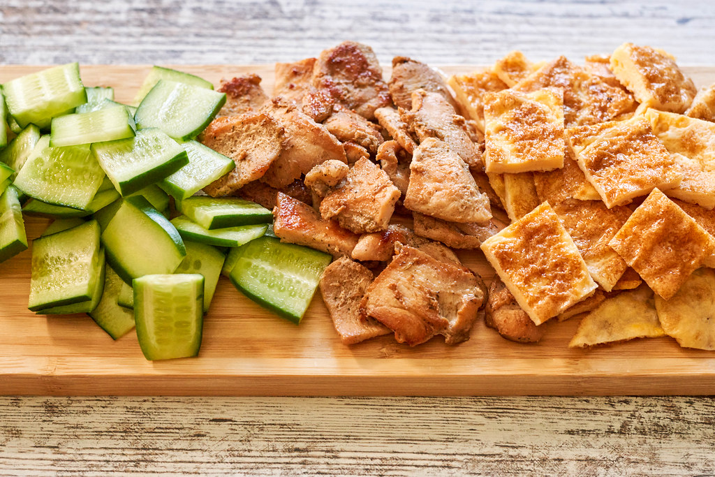 Healthy salad ingredients - cucumber, fried chicken fillet and egg omelet slices